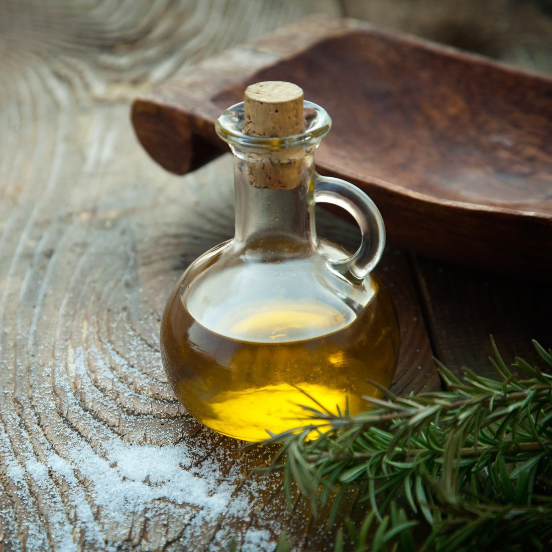 Extra virgin healthy Olive oil with fresh rosemary on rustic wooden background